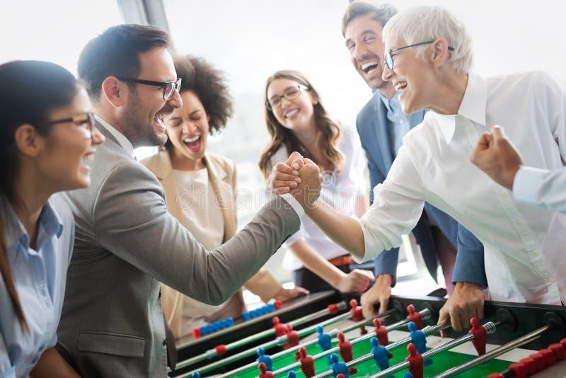 享受滑稽的活动的激动的不同的雇员在工休,创造性的友好的工作者打比赛 免版税库存图片