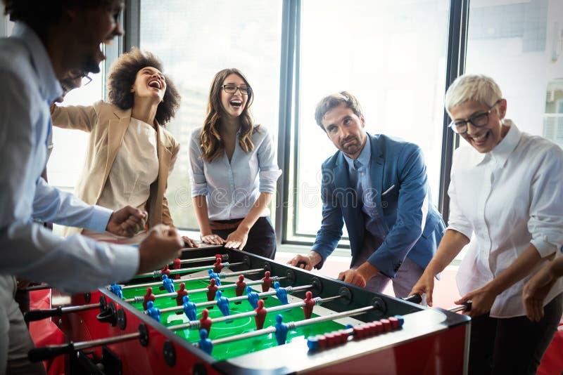 享受滑稽的活动的激动的不同的雇员在工休,创造性的友好的工作者打比赛 图库摄影