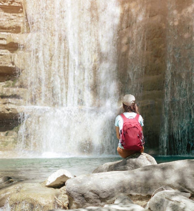 享受瀑布的看法女性探险家 免版税图库摄影