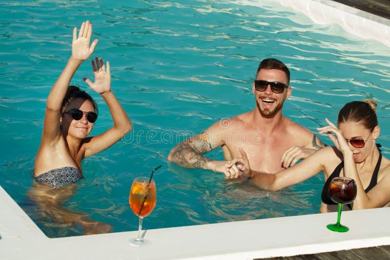 享受热的夏日的朋友在游泳池边 免版税库存图片