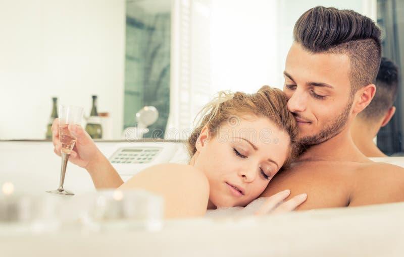 享受热水澡的年轻愉快的成功的夫妇 库存图片