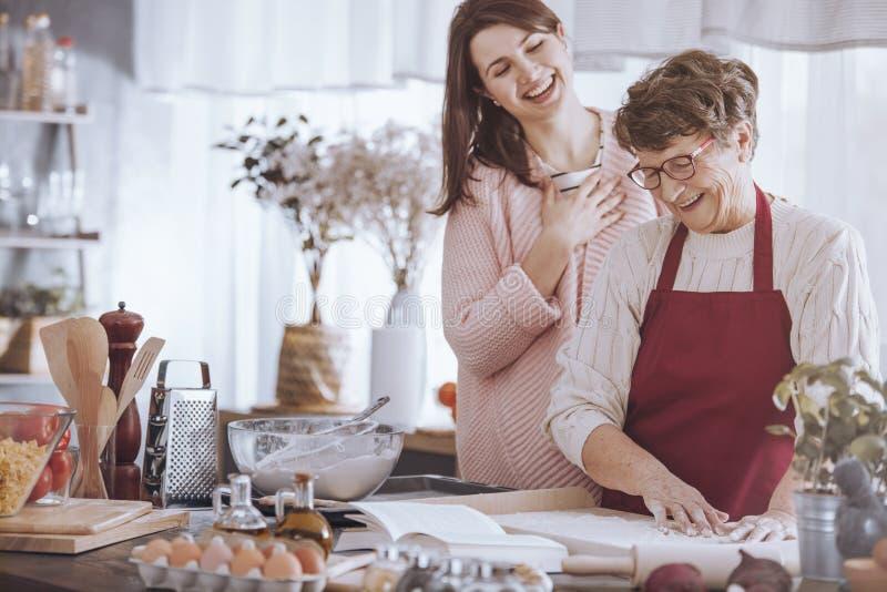享受烹调与祖母的孙女 库存照片