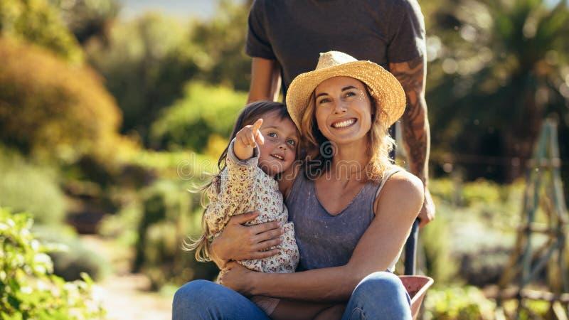 享受独轮车乘驾的家庭在农场 免版税库存图片