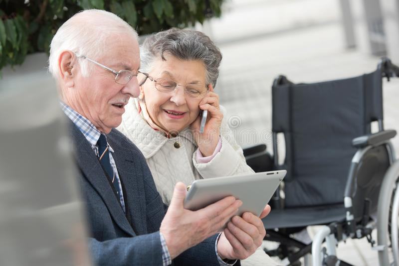 享受现代技术的资深夫妇使用片剂和手机 免版税库存图片