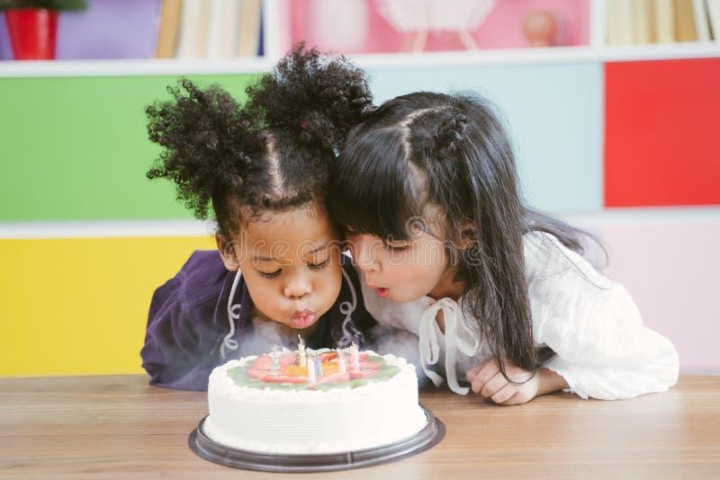 享受生日宴会的孩子吹灭在蛋糕的蜡烛 免版税库存照片
