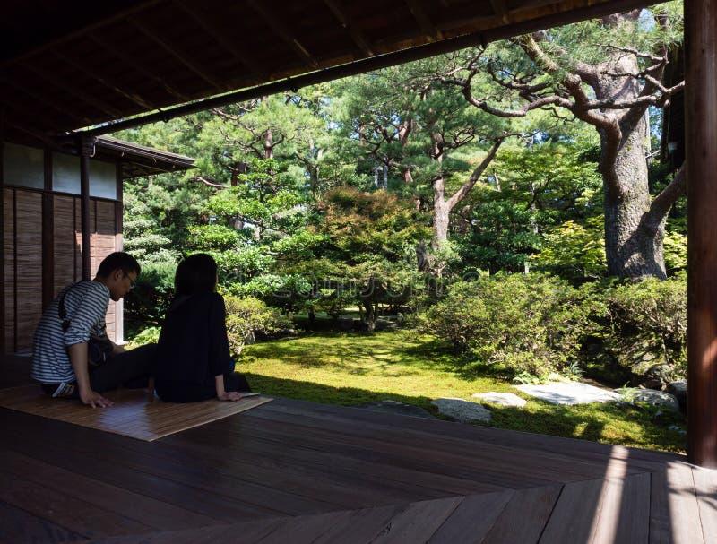 享受看法的夫妇在传统日本庭院里 库存照片