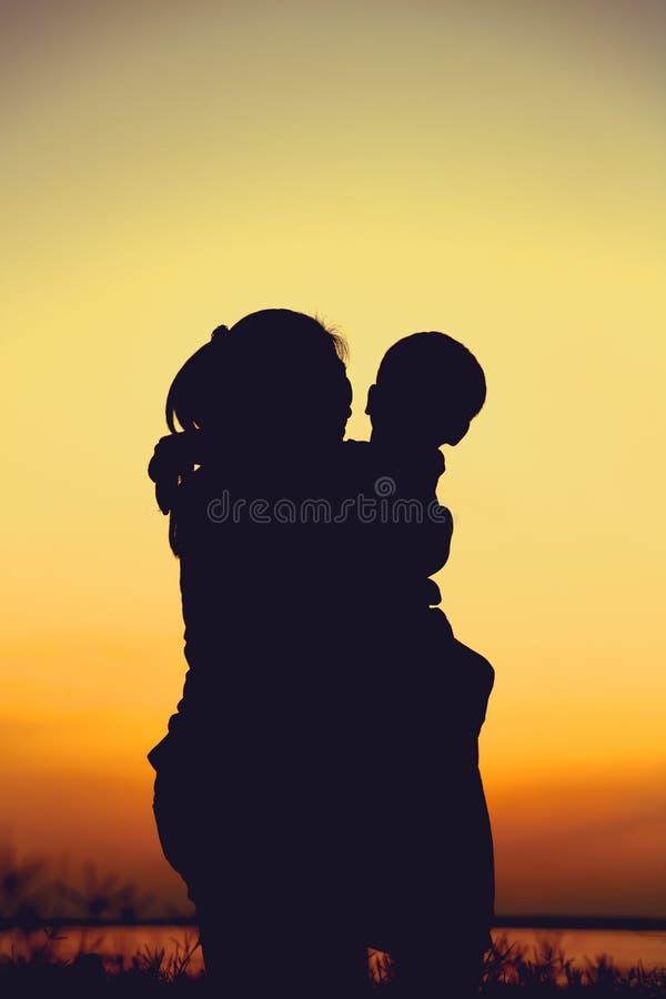 享受看法的母亲和孩子剪影在河沿 免版税库存照片