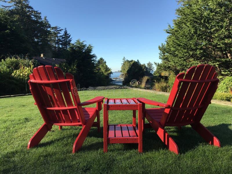 享受看法的红色阿迪朗达克椅子在Tofino, BC 免版税库存照片
