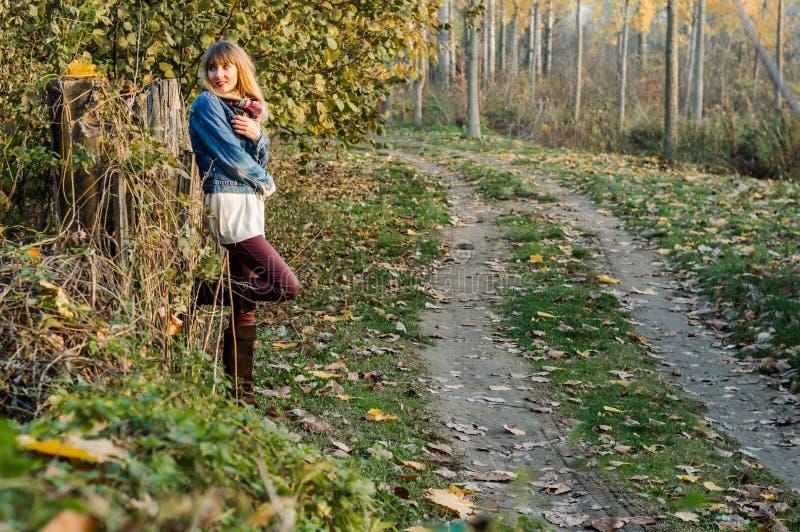 享受秋天季节的白肤金发的女孩 免版税库存图片