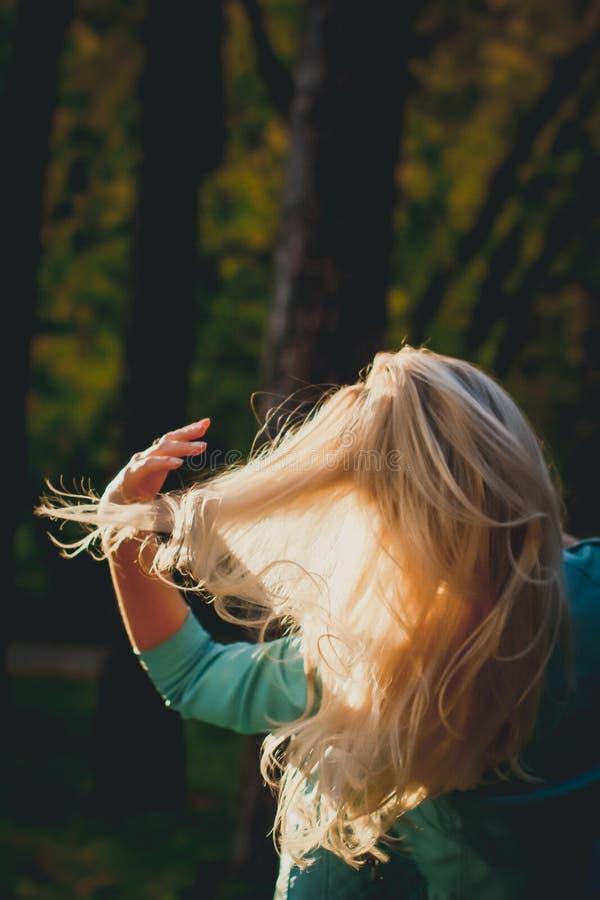 享受秋天的一美丽的年轻女人的画象在公园 可爱的金发碧眼的女人在公园在秋天反对a 免版税库存图片