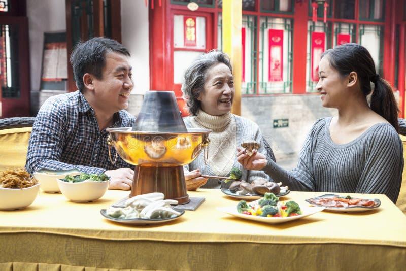享受繁体中文膳食的家庭 库存照片