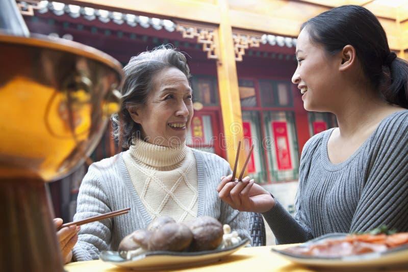 享受繁体中文膳食的母亲和成人女儿 图库摄影