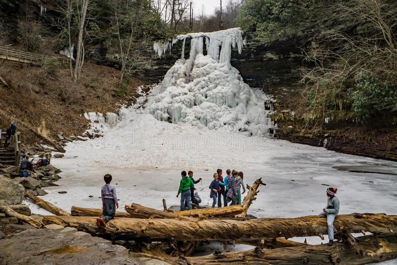 享受结冰的小瀑布秋天的孩子 库存照片
