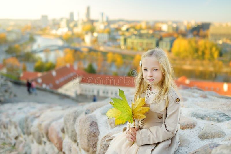 享受维尔纽斯市的看法从格季米纳斯小山的逗人喜爱的女孩在晴朗的秋天天 图库摄影