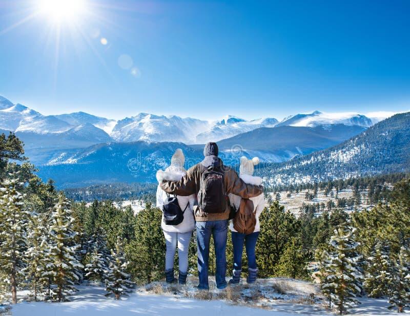 享受美好的冬天山景的幸福家庭 库存照片