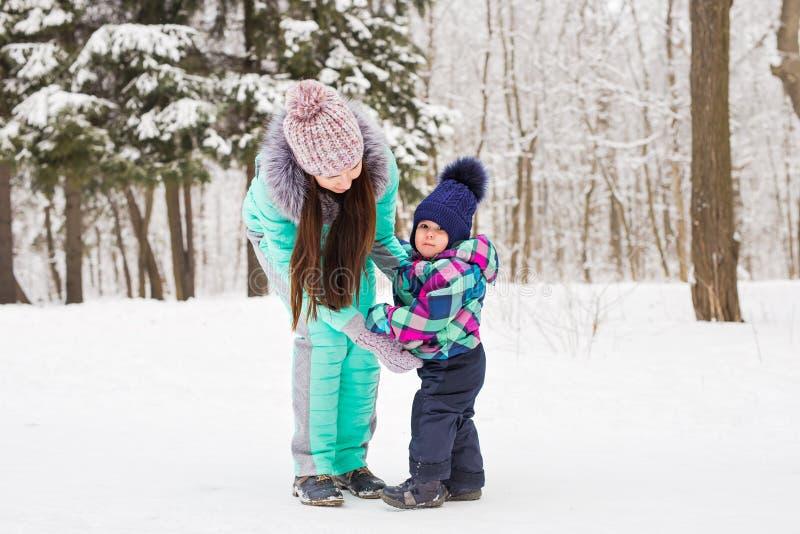 享受美好的冬日的母亲和孩子户外 库存图片