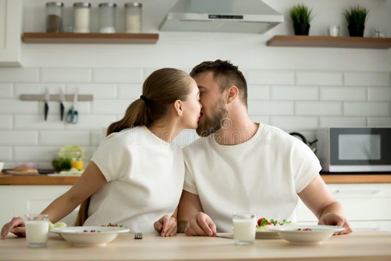 享受膳食亲吻的坐的爱恋的夫妇在用餐厨房ta 库存照片