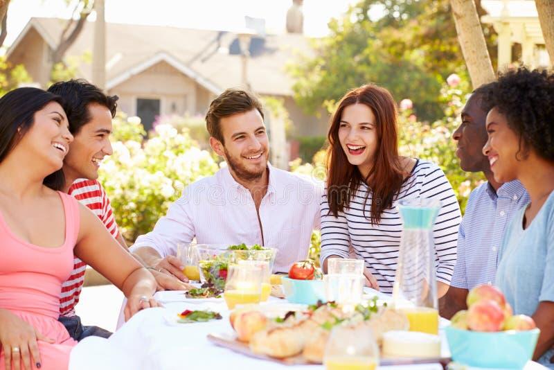 享受膳食的小组朋友在室外党在后院 库存图片