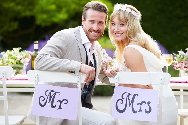 享受膳食的新娘和新郎在结婚宴会 免版税图库摄影