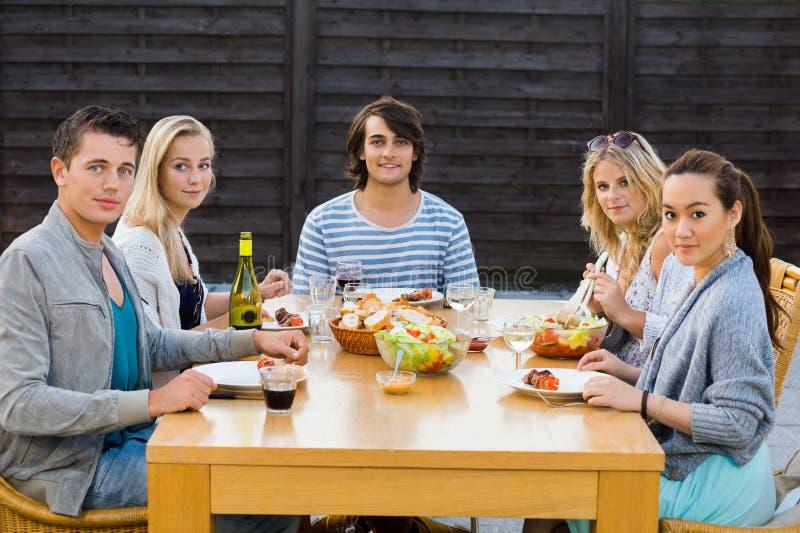 享受膳食的朋友在室外党 免版税库存图片