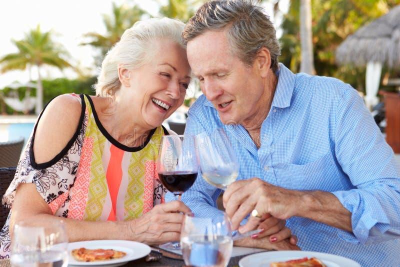 享受膳食的资深夫妇在室外餐馆 免版税库存图片