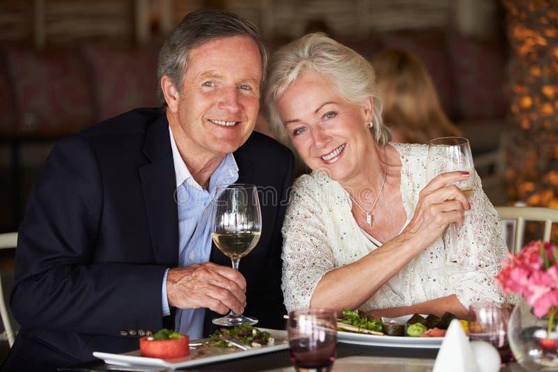 享受膳食的资深夫妇在餐馆 图库摄影