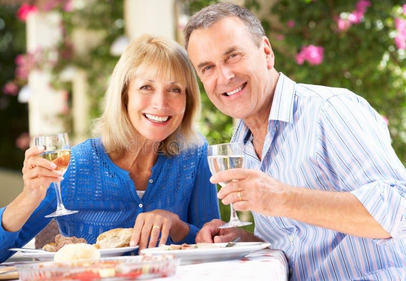 享受膳食的高级夫妇户外 免版税图库摄影