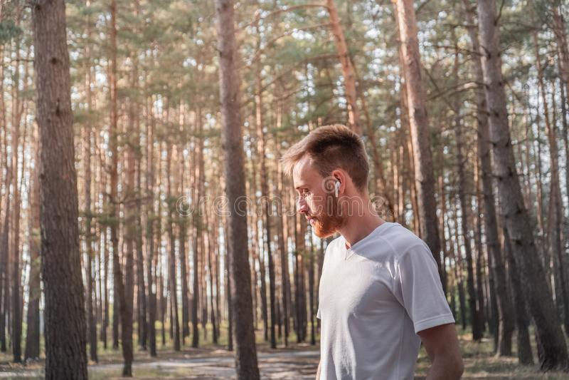享受自然在步行期间或跑步在森林里的年轻人 库存照片