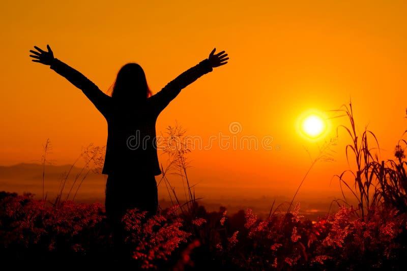 享受自然日落的自由的愉快的妇女 自由,幸福 图库摄影