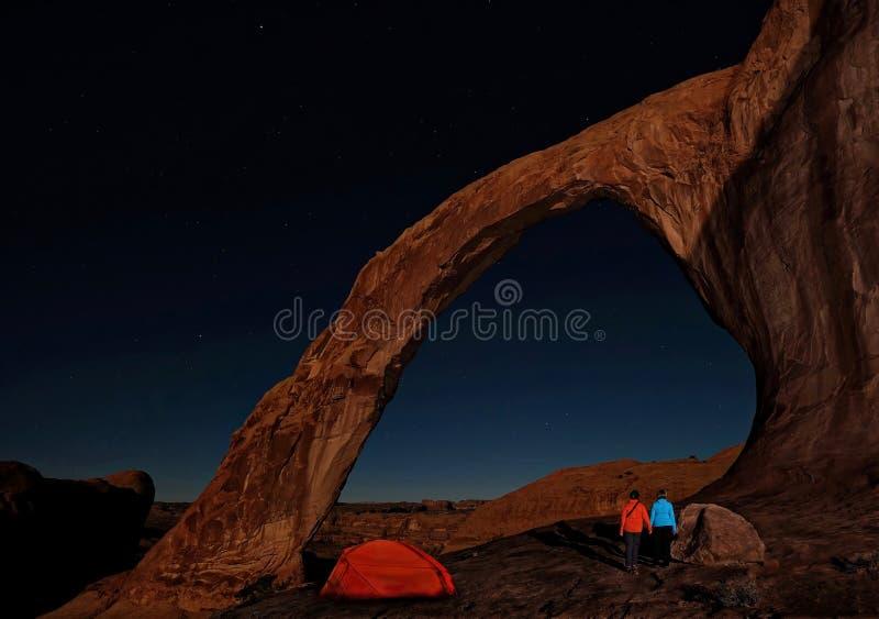 享受自然曲拱和星的看法野营的帐篷和已婚夫妇在晚上 库存照片