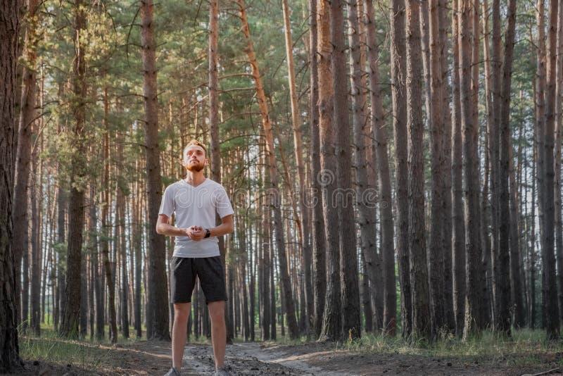 享受自然的年轻人在休息期间在跑步在森林里 库存照片