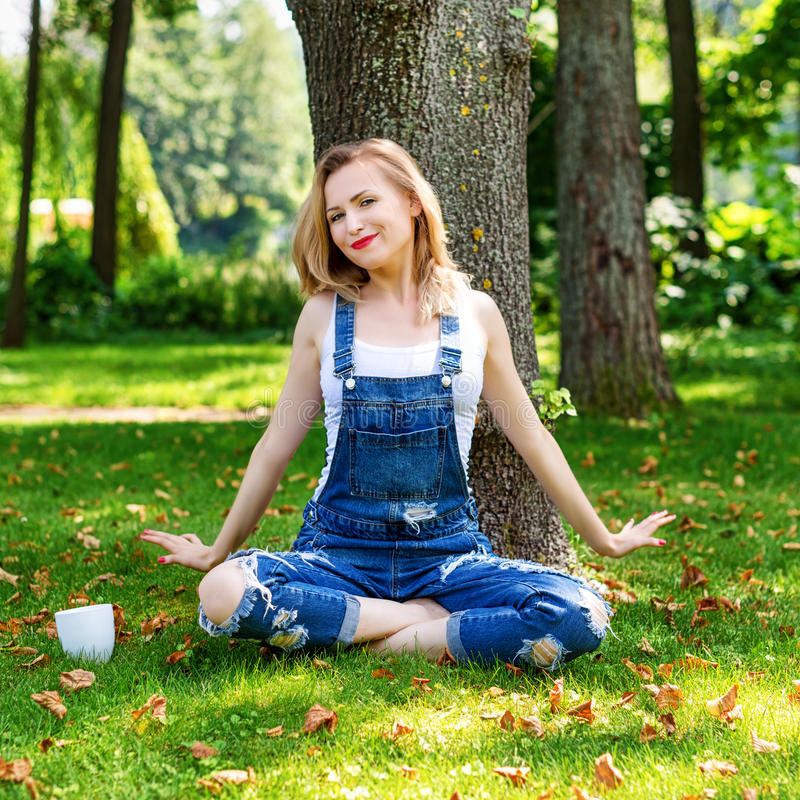 享受自然的愉快的白肤金发的妇女坐与咖啡的绿草 查出的黑色概念自由 免版税库存照片