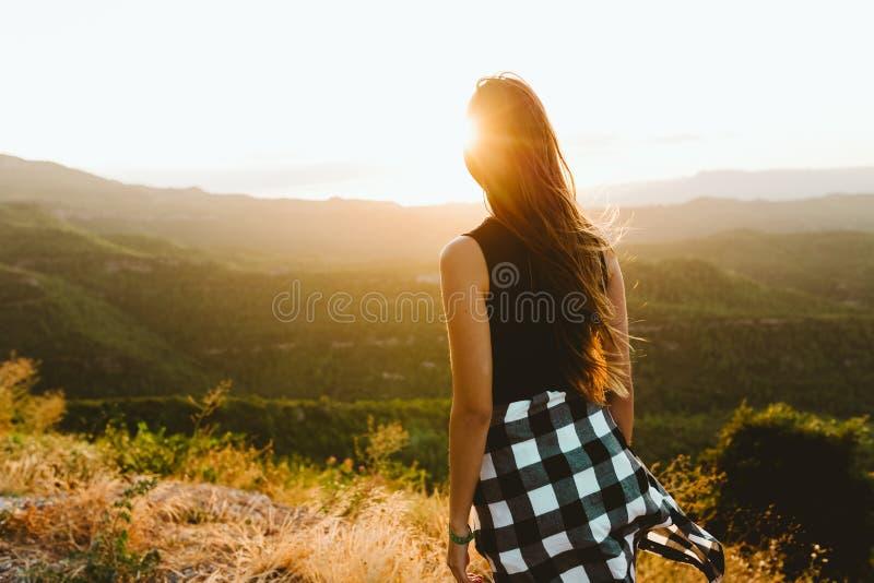 享受自然的美丽的少妇在山峰 免版税库存图片