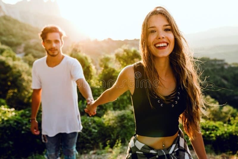 享受自然的美好的年轻夫妇在山峰 库存照片