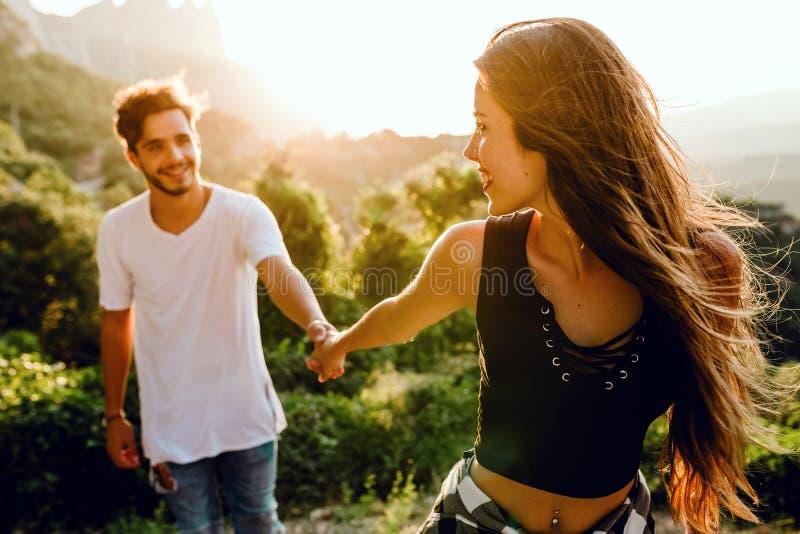 享受自然的美好的年轻夫妇在山峰 图库摄影
