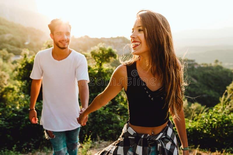 享受自然的美好的年轻夫妇在山峰 免版税图库摄影