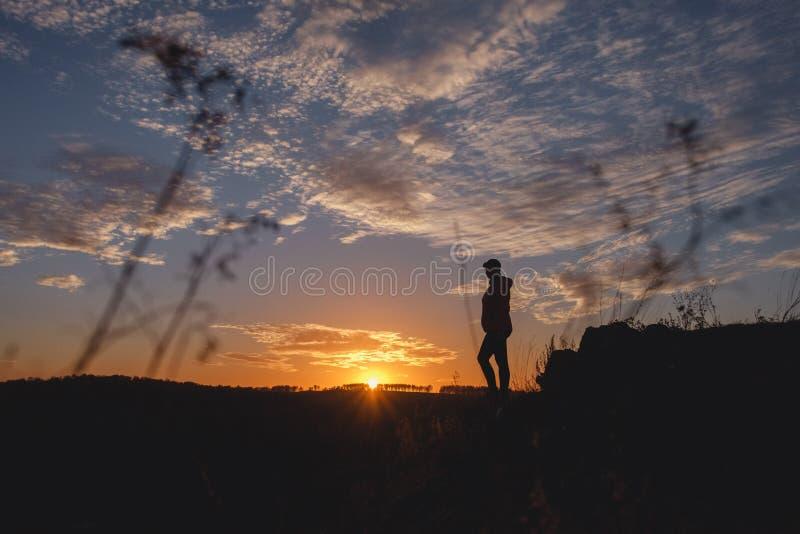 享受自由感觉的自由的妇女剪影愉快在日落 纯净的幸福的平静的松弛妇女 免版税图库摄影