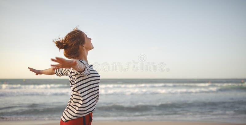 享受自由用在海的开放手的愉快的妇女 库存照片