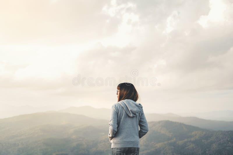 享受自由的愉快的妇女在与日落放松概念的山顶部 图库摄影