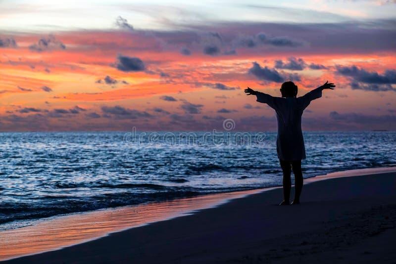 享受自由的自由的妇女剪影感到愉快在海滩 库存照片