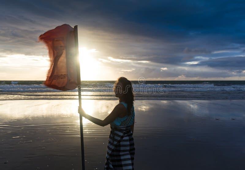 享受自由的自由的妇女感到愉快在海滩在日落 纯净的幸福的美丽的平静的松弛妇女和 免版税库存照片