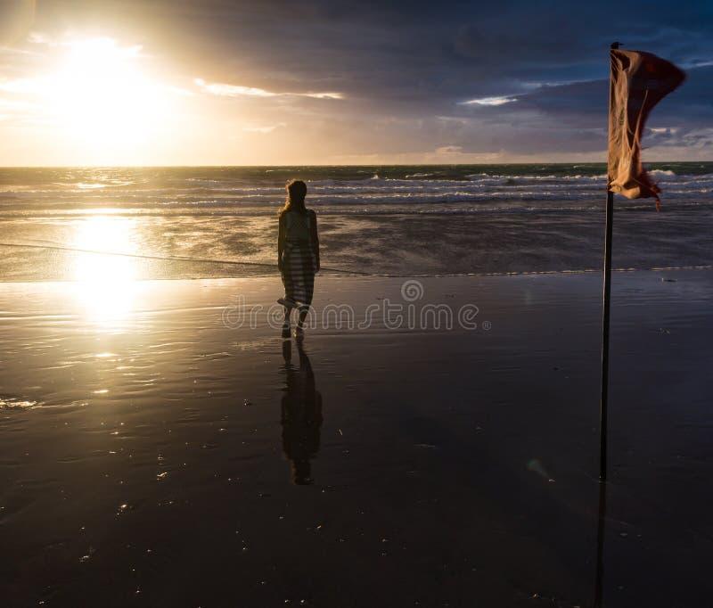 享受自由的自由的妇女感到愉快在海滩在日落 纯净的幸福的美丽的平静的松弛妇女和 免版税库存图片