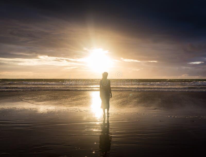 享受自由的自由的妇女感到愉快在海滩在日落 纯净的幸福的美丽的平静的松弛妇女和 库存图片