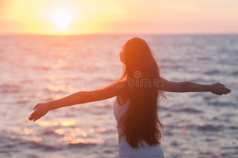 享受自由的自由的妇女感到愉快在海滩在日落。 免版税库存照片
