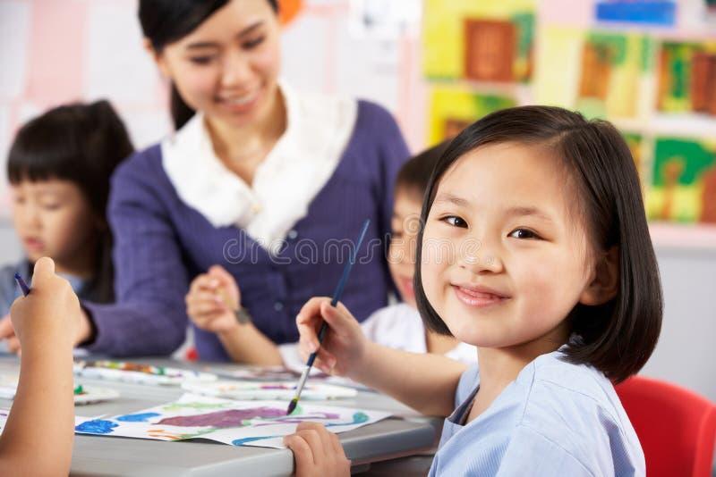 享受艺术课的女性学生在中国学校 免版税库存图片