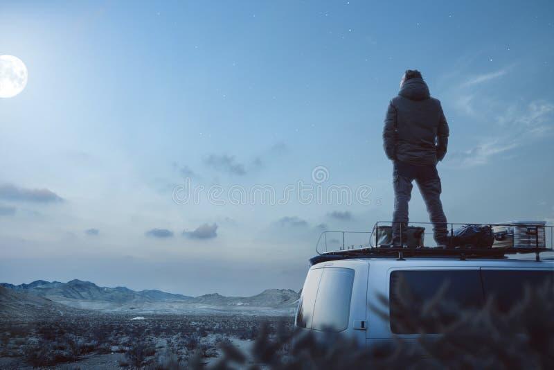 享受被月光照亮夜的年轻人在他的露营者货车顶部 免版税库存图片