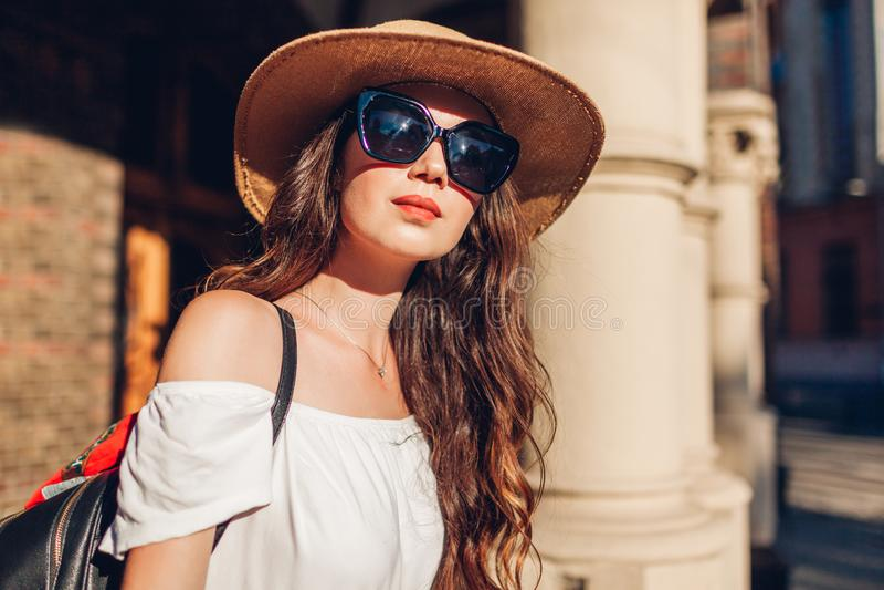 享受观光的年轻时髦的妇女室外画象在利沃夫州 女孩帽子太阳镜佩带 免版税库存图片