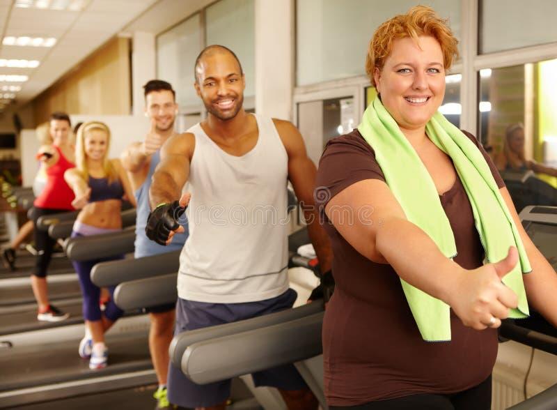 享受训练在健身房的肥胖妇女 库存照片