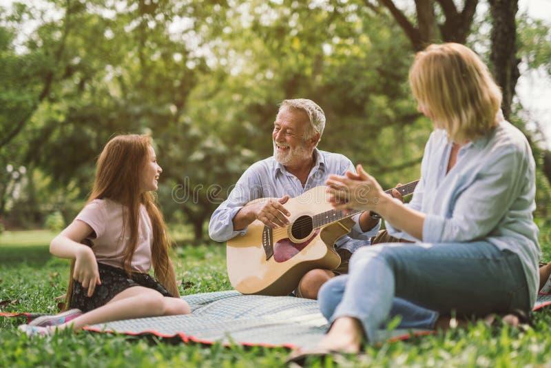 享受质量时间的家庭,弹吉他在他们的绿色公园庭院里 免版税图库摄影