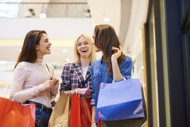享受购物的三个女孩在购物中心 库存图片